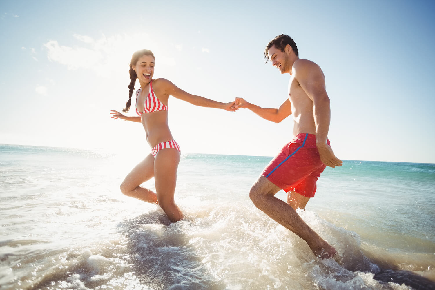 couple running through water at the beach, healthy skin and beautiful body