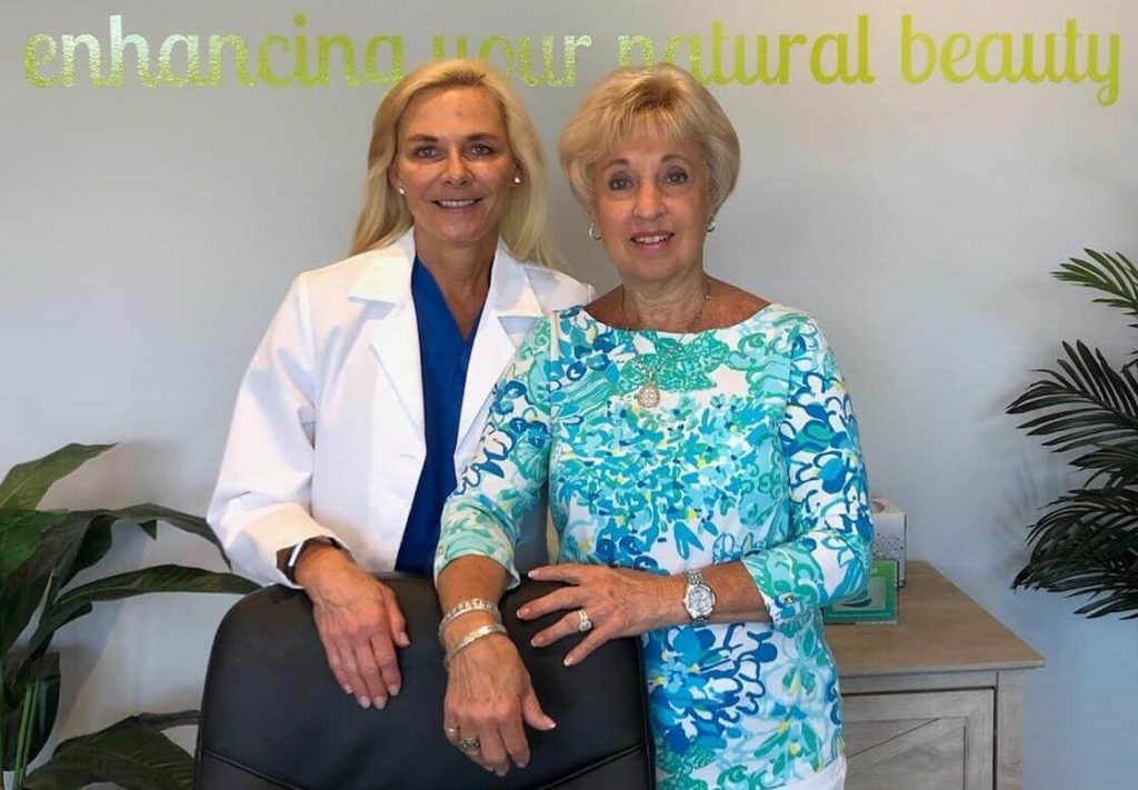 two woman posing behind receptionist's desk, med spa staff