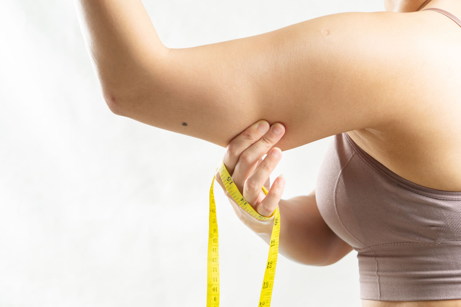 woman pinching excessive arm fat, for skin tightening